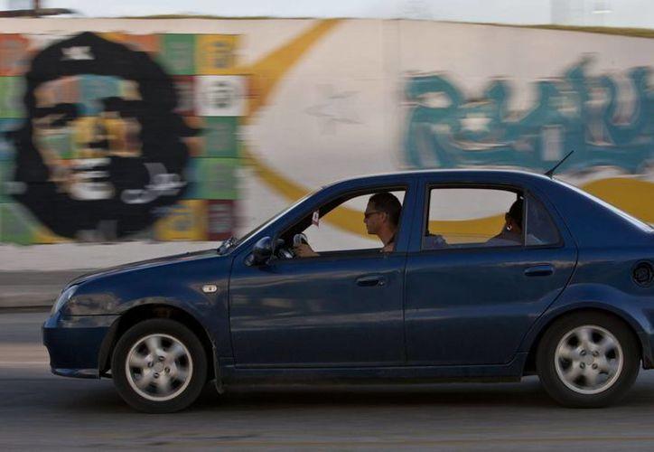 un auto de fabricación china pasa frente a un mural del Che Guevara. La Habana, Cuba. (Agencias)