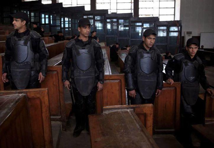 Policías egipcios hacen guardia delante de la jaula donde se encuentran los integrantes de la Hermandad Musulmana condenados a muerte. (Agencias)