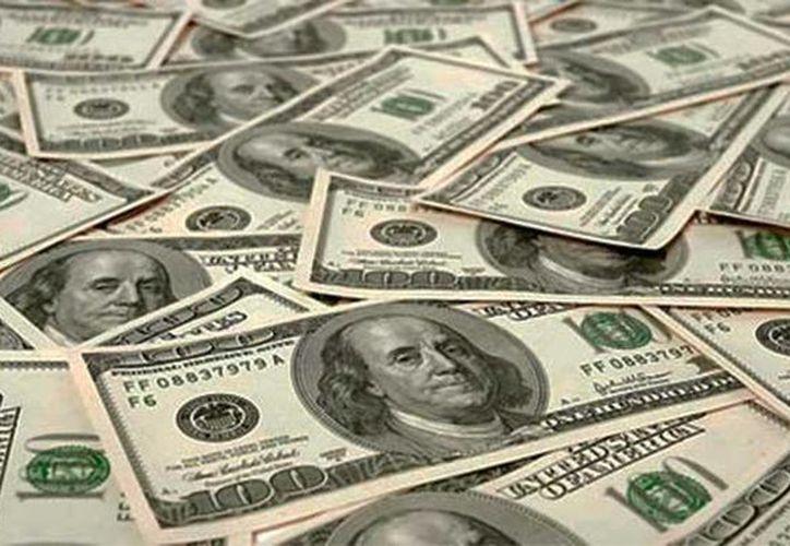 El dinero fue encontrado en el interior una mochila con varios fajos de billetes que sumaban 59 mil 890 dólares, destacó la policía. Imagen de varios billetes de dólares (Archivos/Agencias)
