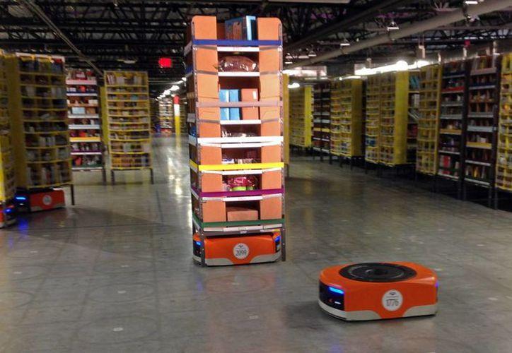 Imagen de un robot Kiva, al frente, antes de transitar entre estanterías de mercancía en el nuevo centro de distribución de Amazon en Tracy, California. (Agencias)