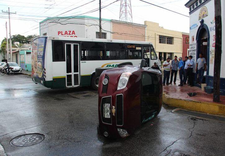Un auto compacto guiado irresponsablemente fue impactado por un autobús y volcó en calles del centro de Mérida. Por fortuna nadie salió herido de gravedad. (Aldo Pallota/SIPSE)