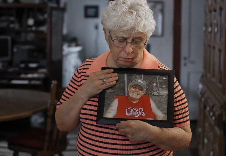 Kay Taynor muestra una foto de su esposo Gary, quien se suicidó luego de que una clínica le diagnosticase el mal de Alzheimer. (AP/Paul Sancya)
