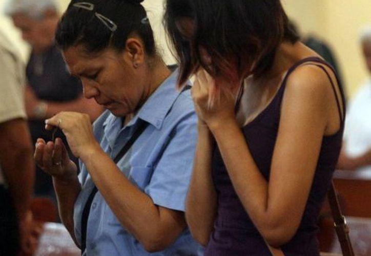 En Yucatán hay mucha devoción de los santos arcángeles. Imagen de contexto de dos mujeres rezando en una iglesia. (Milenio Novedades)