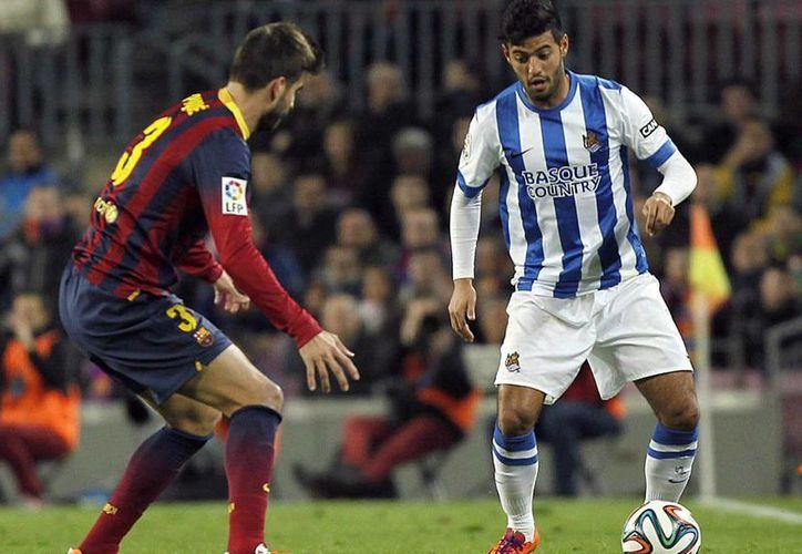 El delantero mexicano de la Real Sociedad, Carlos Vela (d), controla el balón ante el defensa del F. C. Barcelona, Gerard Piqué, durante el encuentro correspondiente a la ida de la semifinal de la Copa del Rey. (EFE)