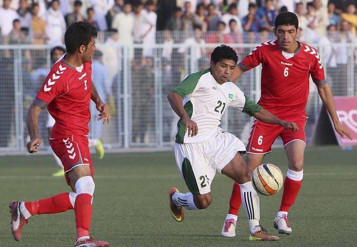 Jugadores afganos (de rojo) pelean por el control del balón contra un pakistaní durante el partido amistoso. (EFE)