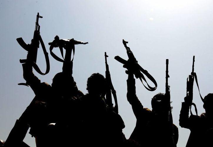 Yemeníes armados, fieles a los rebeldes hutíes, levantan sus armas en Saná, Yemen. (EFE)