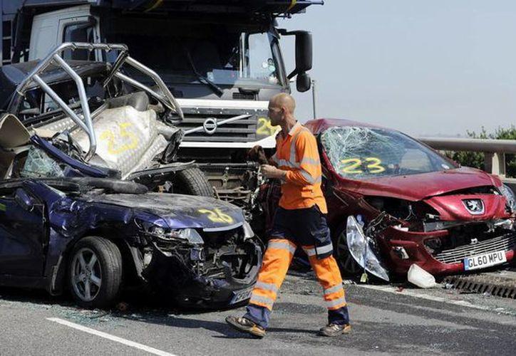 Un trabajador inspecciona varios coches destrozados por el accidente. (EFE)