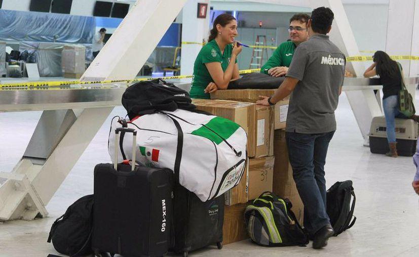 Entre otros objetos, no se permite llevar en el equipaje de mano líquidos, geles y aerosoles en cantidades mayores a 100 mililitros. Imagen de contexto de viajeros en el Aeropuerto Internacional de la Ciudad de México. (Archivo/Notimex)