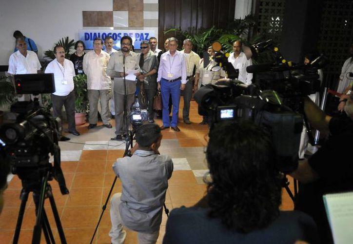 """El jefe negociador de las FARC, Luciano Marín (c), alias """"Iván Márquez"""", lee un comunicado a la llegada del equipo negociador de esta guerrilla al Palacio de Convenciones de La Habana, Cuba. (EFE)"""