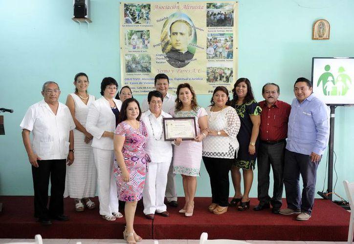 La Presidenta del DIF Yucatán, con el galardón que le otorgó la asociación Yermo y Parres, A.C., acompañada de varios integrantes de la organización. (Milenio Novedades)