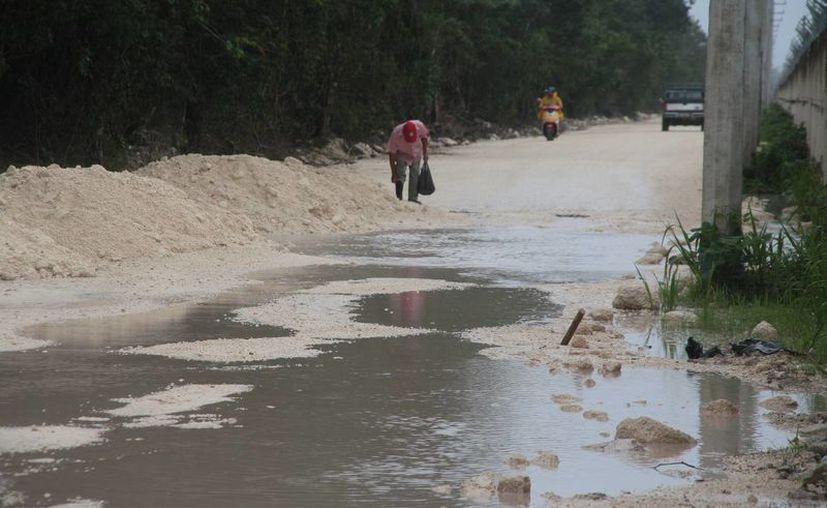 Las personas que circulan por el camino de acceso deben de sortear los baches y montículos de material pétreo. (Julián Miranda/SIPSE)