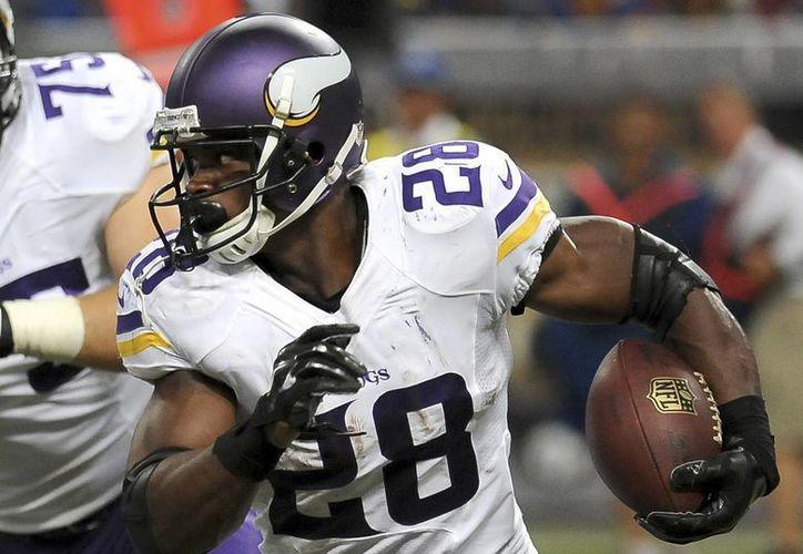 Adrian Peterson, running back de Vikings de Minnesota, acarrea  la pelota contra St. Louis Rams durante el tercer cuarto de un partido jugado el 7 de septiembre del año en curso. (Foto: AP)