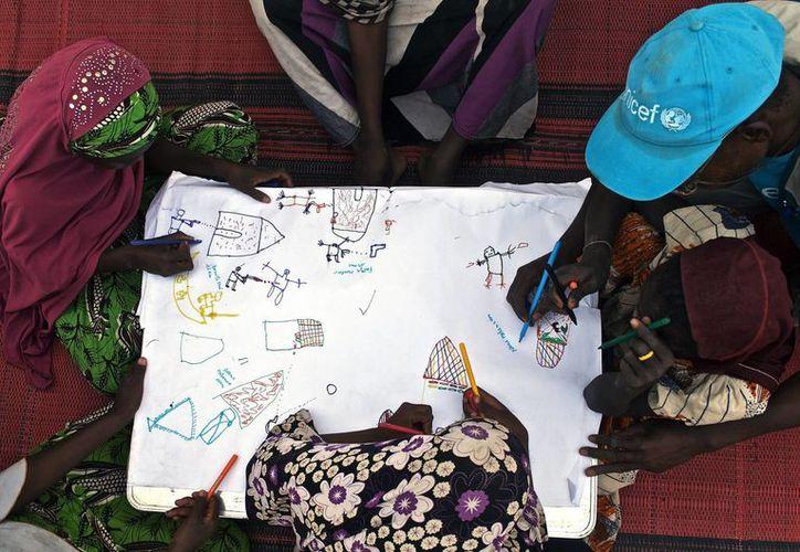 Un grupo de niños dibuja sus experiencias con Boko Haram con la ayuda de un voluntario de Unicef en el campo de refugiados de Dar es Salam, Chad. (Archivo/EFE)