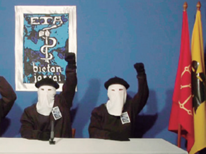 Masked members of the Basque separatist group ETA raise their fists in unison following a news conference at an undisclosed location. (AP).