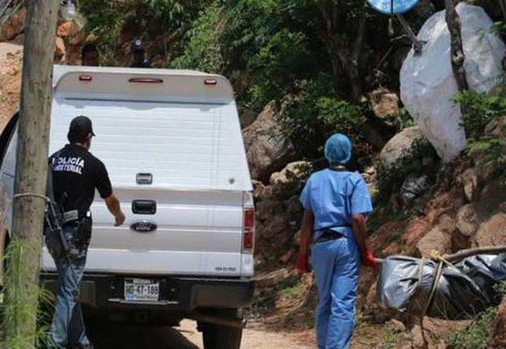Familiares rechazan que los cadáveres encontrados sean de los dos médicos y dos licenciados desaparecidos. Imagen del levantamiento de un cuerpo en Acapulco.(noticiasacapulconews.com)