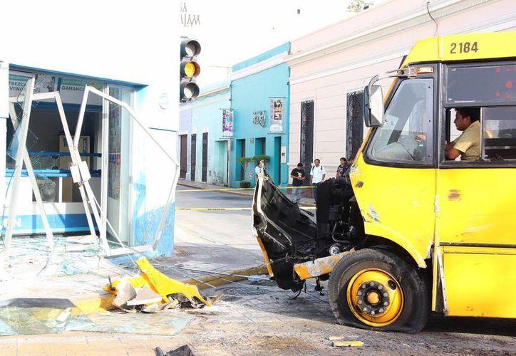 Un choque entre dos autobuses del transporte urbano, de la empresa Minis 2000, en Mérida, dejó saldo de varios heridos y daños materiales no sólo en los vehículos, sino también en algunos comercios. (Aldo Pallota/SIPSE)