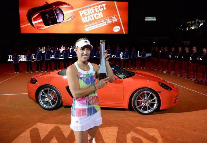 La tenista alemanda Angelique Kerber posa con su trofeo y el automóvil  Porsche Boxster 718 que recibió como recompensa, luego de ganar el Abierto de Stuttgart, ante su compatriota Laura Siegemund. (AP)
