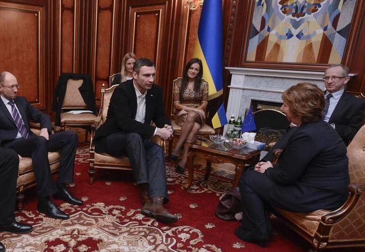 El líder de la oposición ucraniana Arseniy Yatsenyuk (izquierda) y el legislador y dirigente del partido Udar, el excampeón de boxeo Vitali Klitschko (centro) conversan con la jefa de política exterior de la Unión Europea Catherine Ashton (derecha) en Kiev. (Agencias)