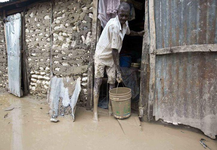 Un hombre sala lodo de su vivienda tras el paso del huracán 'Matthew', en Les Cayes, Haití. (AP/Dieu Nalio Chery)