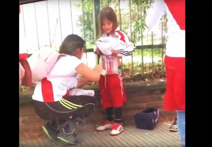 Una aficionada de River Plate oculta pirotecnia en el torso de una niña y es captada en video que circula en redes sociales. (Captura de video)