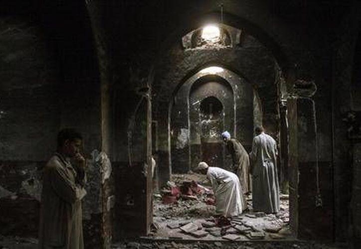 Cristianos egipcios liampian la dañada capilla del ancestral Monasterio de la Virgen María y San Abraham, que fue saqueada y quemada por islamistas, en Dalga. (Agencias)