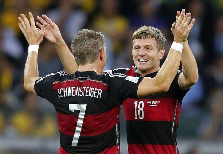 Bastian Scweinsteiger felicita a Toni Kroos, quien anotó por Alemania frente a Brasil en la semifinal de la Copa del Mundo, en Belo Horizonte (AP Foto/Frank Augstein)