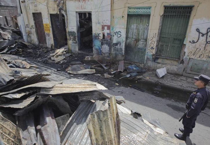 Un miembro de la Policía Nacional Civil permanece entre los escombros de una vivienda destruida por un incendio registrado en un sector céntrico de San Salvador. (EFE)