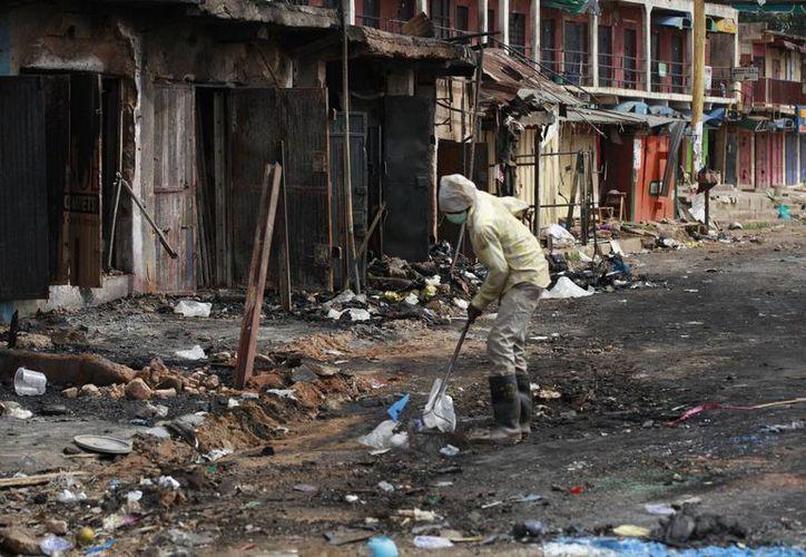 Un empleado realiza labores de limpieza en un sitio donde explotó un carro-bomba en la ciudad nigeriana de Jos. (Foto: AP/Sunday Alamba)