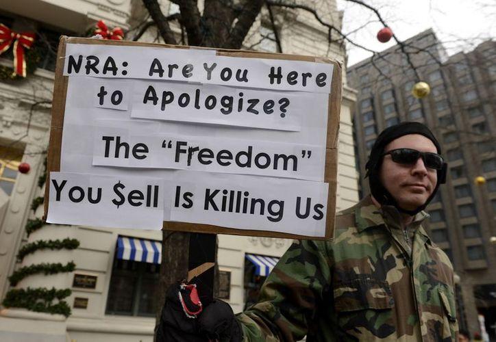 Un hombre sostiene un cartel en contra de la Asociación Nacional del Rifle (NRA) de EU (EFE)