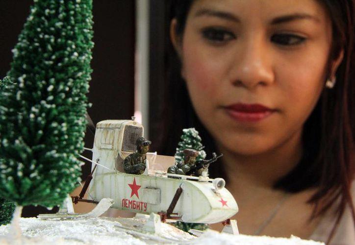 En la foto Reyna Cauich Uc, la única mujer del club Búnker Maya en Yucatán junto con un tanque en miniatura. (Milenio Novedades)