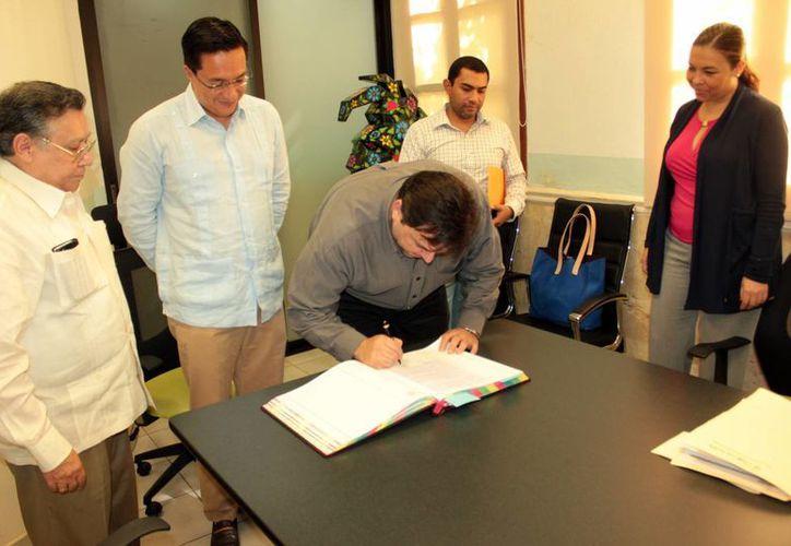 Roberto Rodríguez Asaf estampa su firma en el protocolo del Fideicomiso Público para la Administración de la Reserva Pública de Ucú. (Milenio Novedades)
