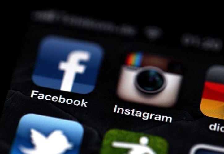 Fotografía de los logos de las aplicaciones Facebook (i) e Instagram (c) en un iPhone. (EFE/Archivo)
