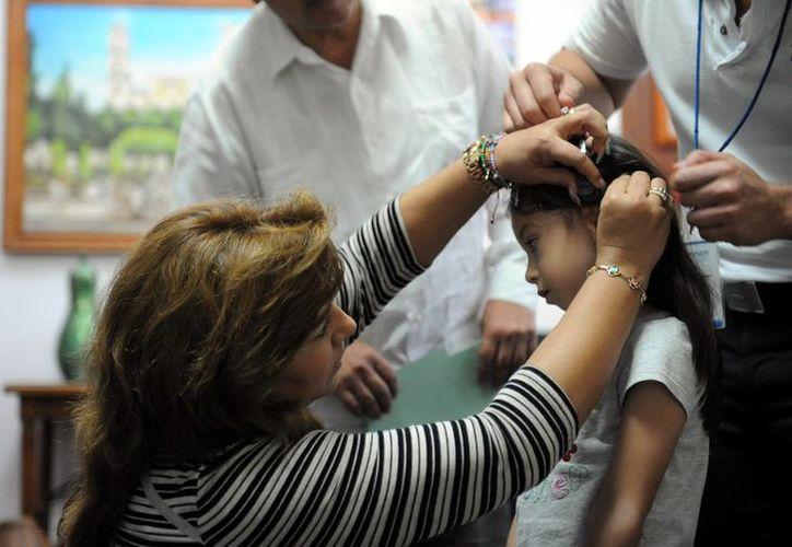 La titular del DIF estatal al momento de colocar un aditamento auditivo a una de las menores beneficiadas. (Milenio Novedades)