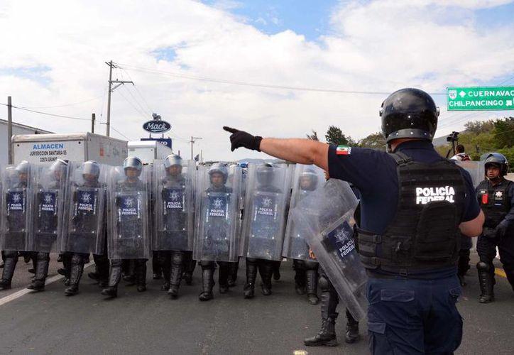 Durante la megamarcha de los maestros de la CETEG fue retenido un elemento policial armado. (Notimex)