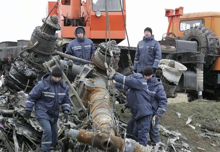 Trabajadores remueven los escombros del avión malasio MH17 que chocó en una zona de la localidad Grabovo, a unos 70 kilómetros de Donetsk, Ucrania. (EFE)