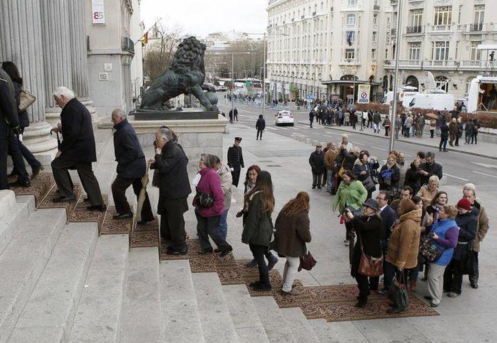 Varias personas hacen fila para entrar a la capilla ardiente del fallecido expresidente Adolfo Suárez, instalada en el salón de pasos perdidos del Congreso en España. (EFE)