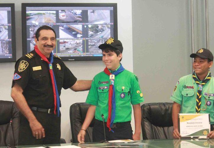 El scout Juan José Alcocer Vilchis (c) quien titular de la SSP por hoy, siendo lobato también fue jefe de Bomberos por un día. (Cortesía)