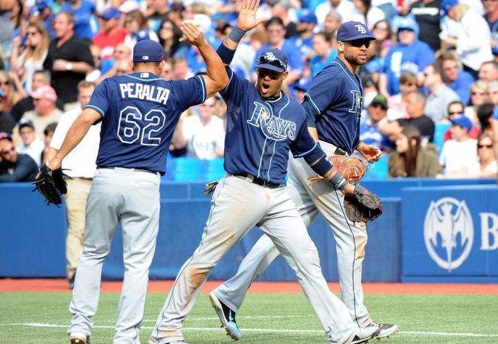 El cubano Yunel Escobar (centro) festeja con sus compañeros, el dominicano Joel Peralta y James Loney, luego de realizar una doble matanza en el juego del domingo, ante los Azulejos de Toronto. (Agencias)