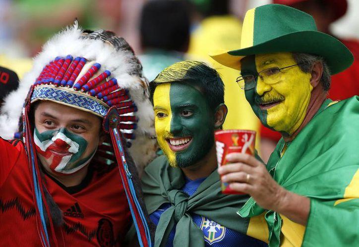 Algunos aficionados mexicanos llegaron al partido contra Brasil solo con máscaras y otros hasta con rostros pintados. (EFE)