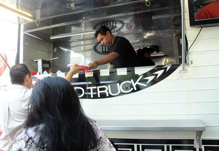 La venta de comida gourmet en vehículos se extiende cada día más en el Estado. Imagen de dos personas al ser atendidas por el personal de un foodtrucks. (Milenio Novedades)