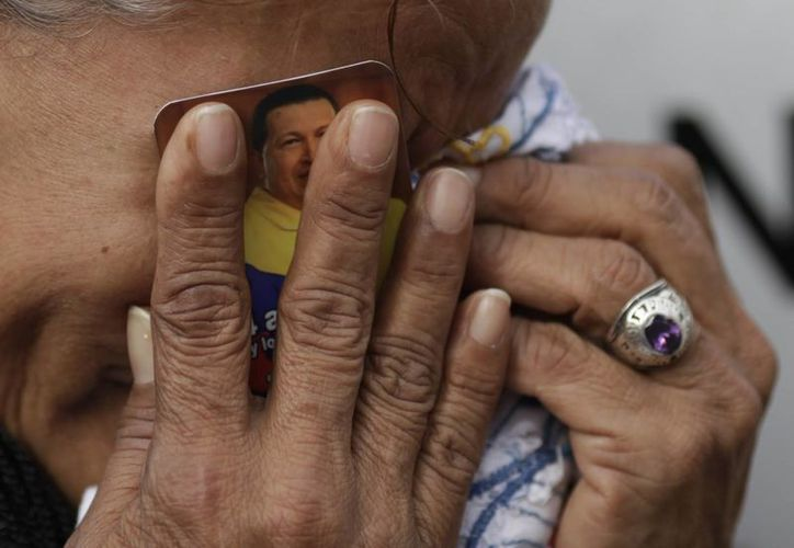 Hugo Chávez, cuya imagen aparece entre las manos de una mujer, tendrá su propia serie de televisión. El que fuera presidente de Venezuela murió en 2013. (Archivo)