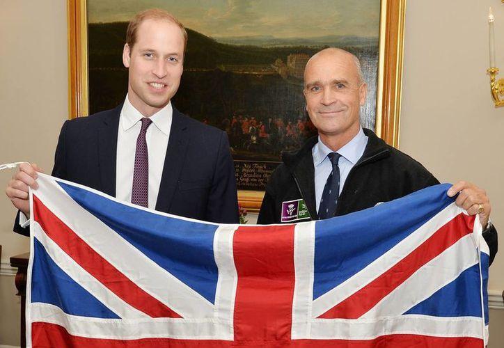 En esta foto de archivo muestra al ex oficial del ejército británico Henry Worsley (der), y al príncipe Guillermo sosteniendo la bandera británica en Londres. (Agencias)
