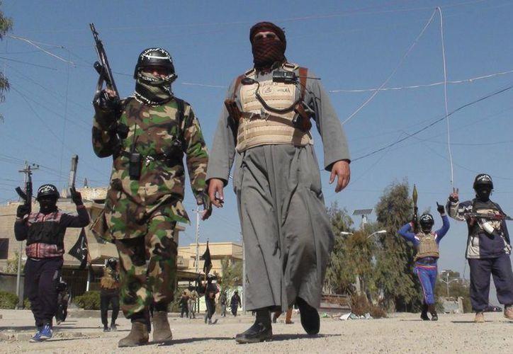 Varios hombres armados caminan por una calle de Faluya, al oeste de Irak, el pasado lunes. (EFE)