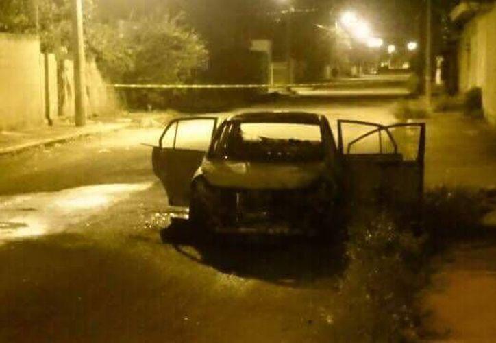 Imagen del auto que desconocidos incendiaron, luego de atacar al chofer, quien trabaja para la plataforma Uber. (SIPSE)