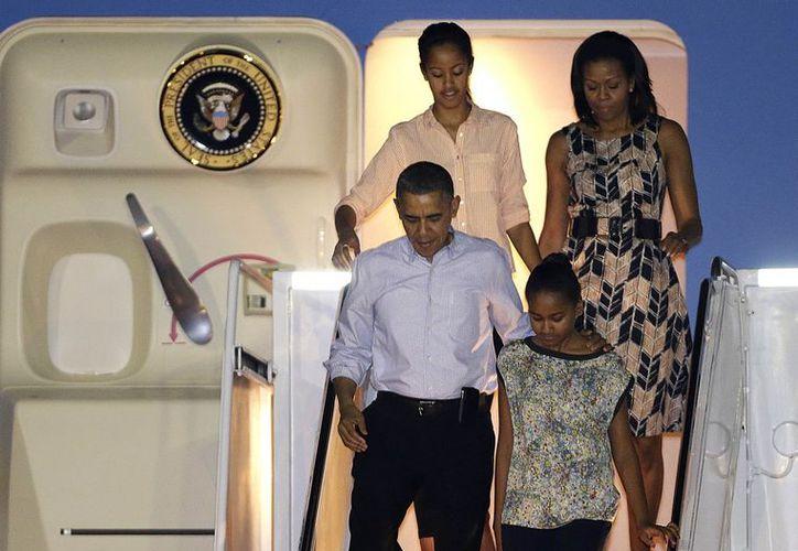 El presidente Barack Obama con la primera dama Michelle Obama y sus hijas Malia (arriba), y Sasha (abajo) (Agencias)