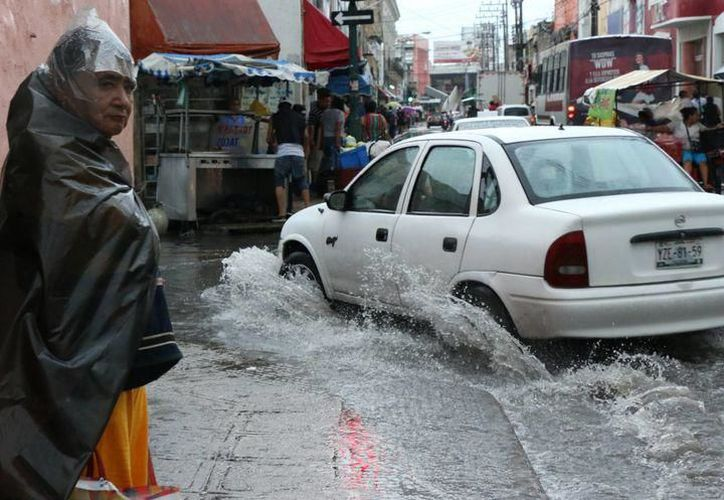 La lluvia registrada ayer en la ciudad, ocasionó por segundo día consecutivo, afectaciones a meridanos, principalmente por calles inundadas. (SIPSE)