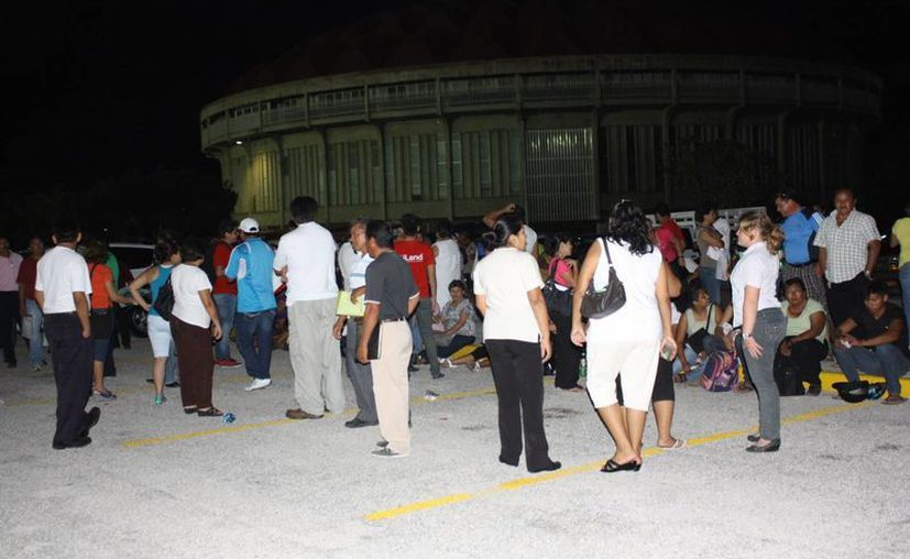 """Cientos de personas se quedaron """"vestidas y alborotadas"""" anoche, esperando la entrega de autos y casas por las que dieron dinero. (Martín González/SIPSE)"""