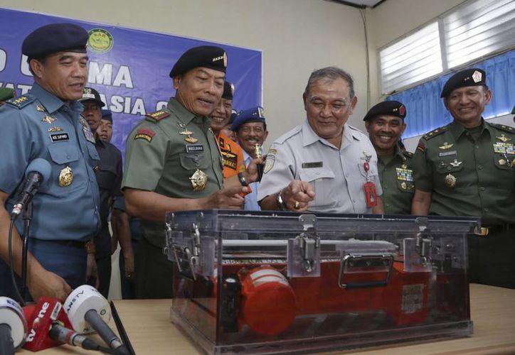 El jefe de las fuerzas armadas de Indonesia, el general Moeldoko (centro izquierda) y el jefe de la Junta Nacional de Seguridad en el Transporte, Tatang Kurniadi (centro derecha), observan una de las cajas negras del avión de AirAsia accidentado en el mar de Java. (Agencias)