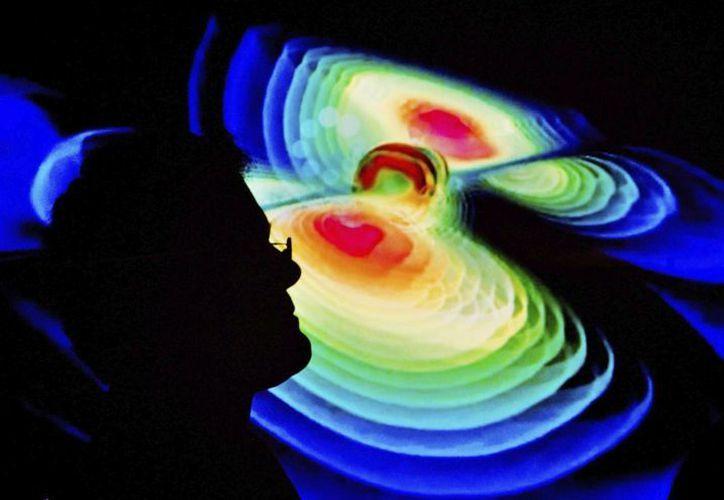 Un científico observa una representación de las ondas gravitacionales durante una rueda de prensa del Instituto de Max Planck de la Física Gravitacional en la universidad Leibniz de Hannover, Alemania. (EFE/Archivo)