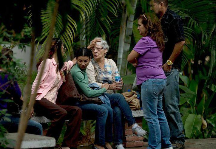 Josefa Alvarez de González, viuda de Rodolfo Gonzalez, es reconfortada por familiares tras conocer la muerte de su marido, quien se habría suicidado en prisión. (AP)